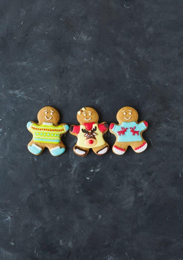 Uomini dello zenzero con la glassa colorata su un fondo grigio gingerbread Biscotti di natale fotografie stock libere da diritti