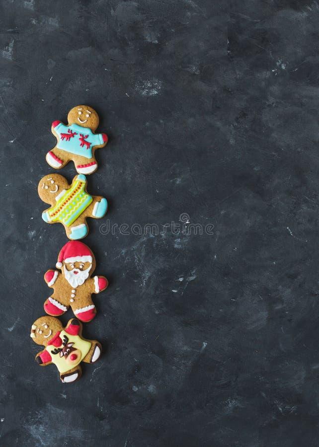 Uomini dello zenzero con la glassa colorata su un fondo grigio gingerbread Biscotti di natale immagini stock