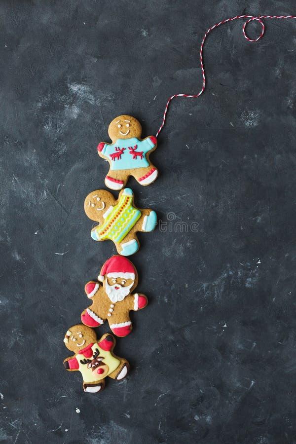 Uomini dello zenzero con la glassa colorata su un fondo grigio gingerbread Biscotti di natale immagine stock