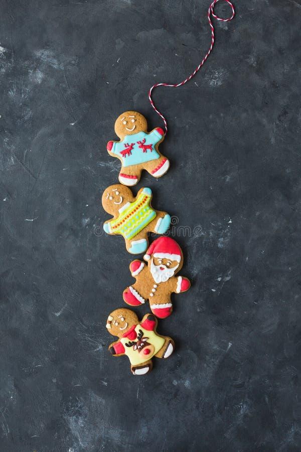 Uomini dello zenzero con la glassa colorata su un fondo grigio gingerbread Biscotti di natale immagini stock libere da diritti