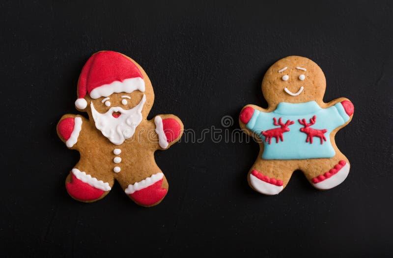 Uomini dello zenzero con la glassa colorata su un fondo nero gingerbread fotografia stock libera da diritti