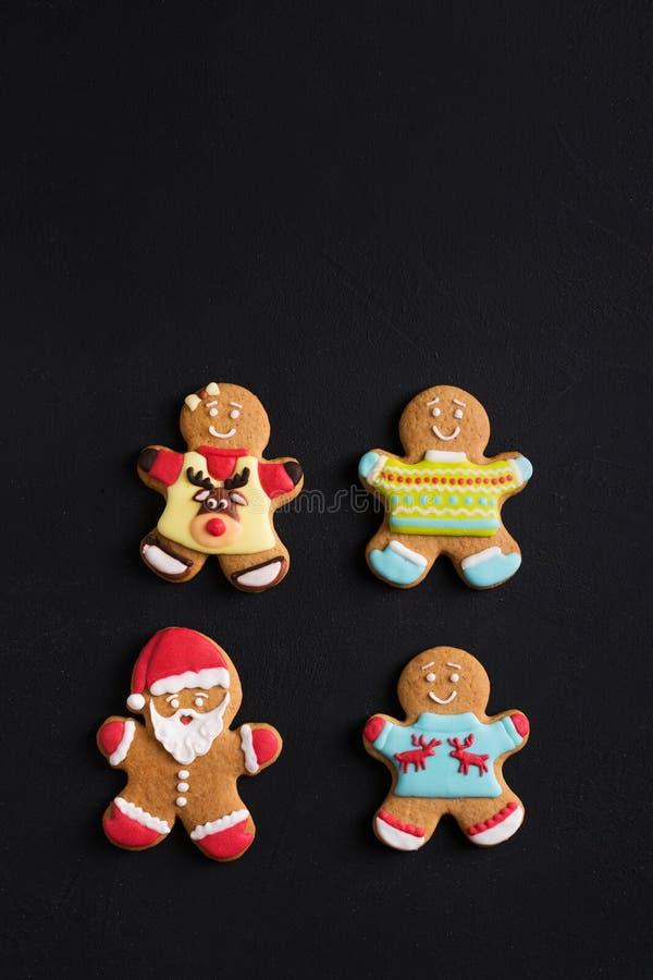 Uomini dello zenzero con la glassa colorata su un fondo nero gingerbread immagine stock libera da diritti