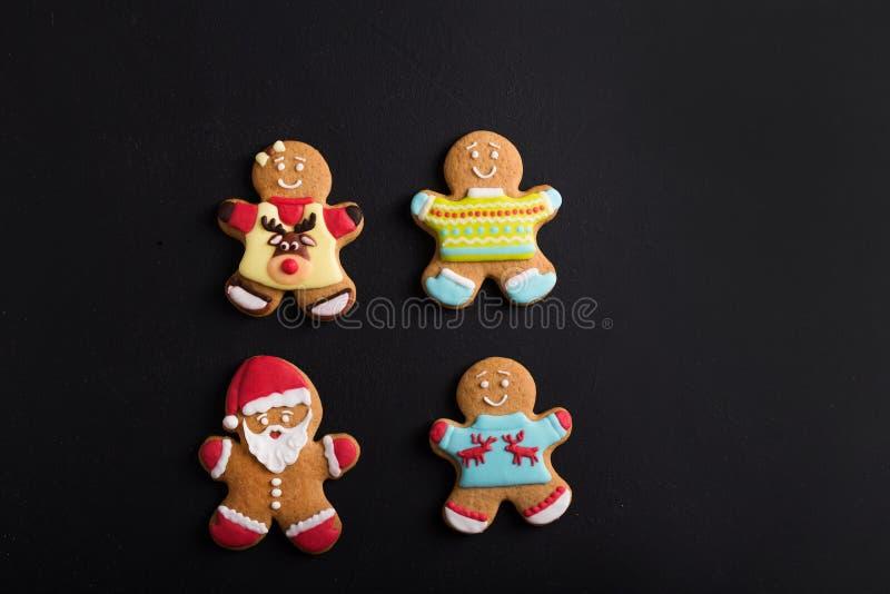 Uomini dello zenzero con la glassa colorata su un fondo nero gingerbread fotografia stock