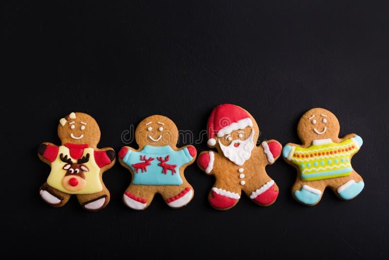 Uomini dello zenzero con la glassa colorata su un fondo nero gingerbread immagini stock