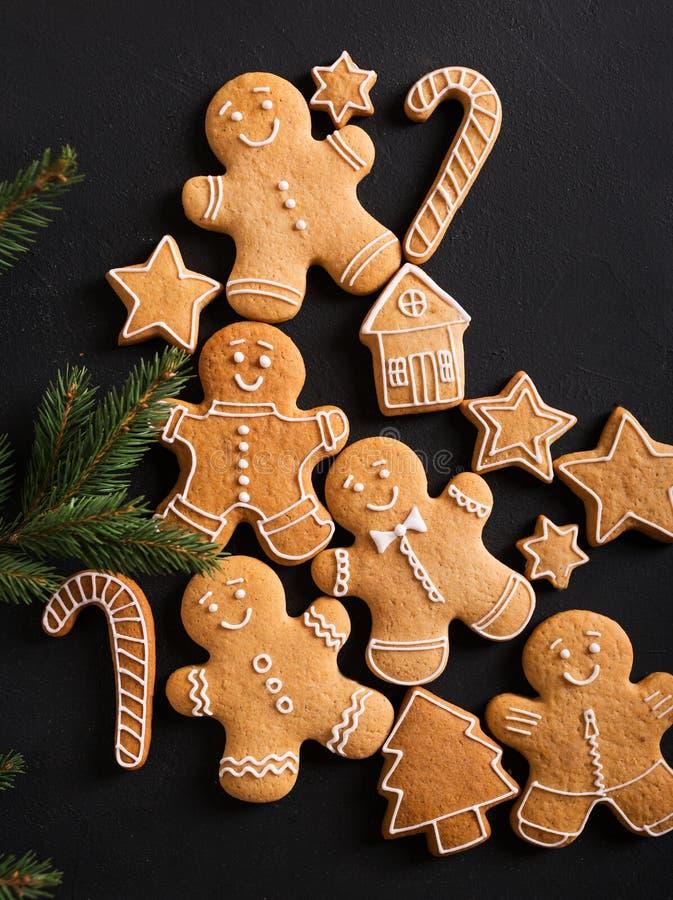 Uomini dello zenzero con la glassa su un fondo nero gingerbread Biscotti di natale fotografia stock libera da diritti