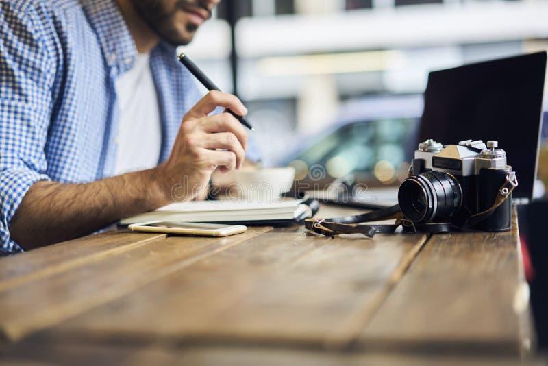Uomini di affari in camicia blu che si siede alla tavola di legno con attrezzatura fotografie stock libere da diritti