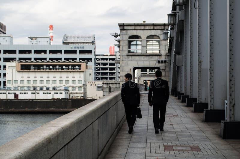 Uomini di affari che attraversano il ponte di Kachidoki a Tokyo fotografia stock libera da diritti
