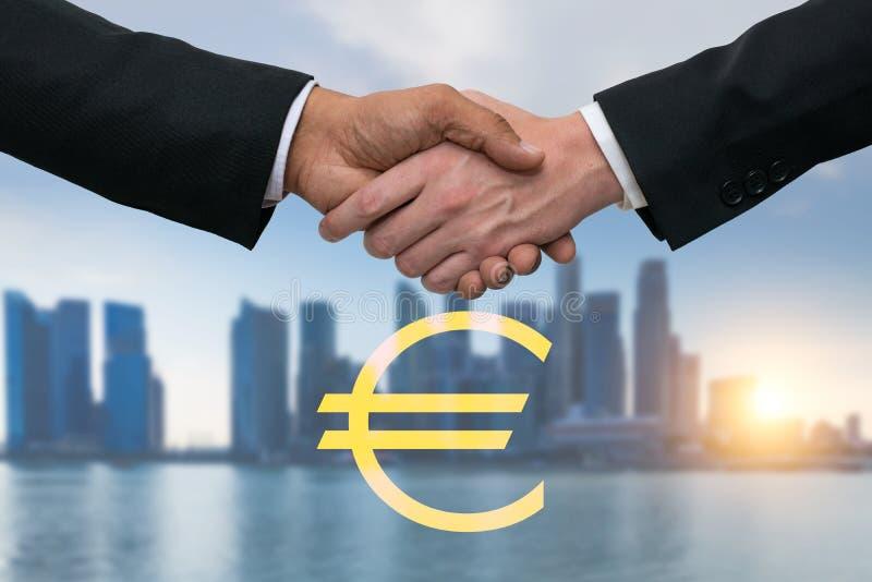 Uomini di affari che stringono le mani per l'affare con euro soldi Orizzonte delle costruzioni nel fondo fotografia stock