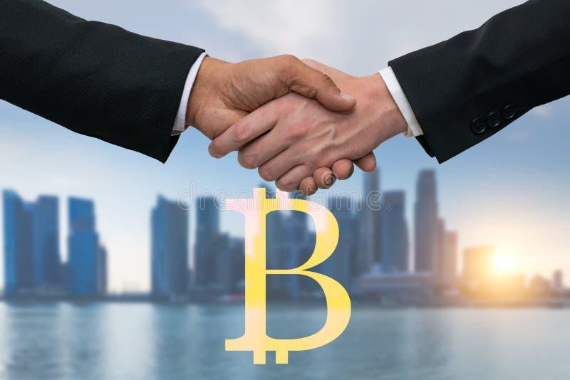 Uomini di affari che stringono le mani per l'affare con i soldi dei bitcoins Orizzonte delle costruzioni nel fondo immagine stock libera da diritti