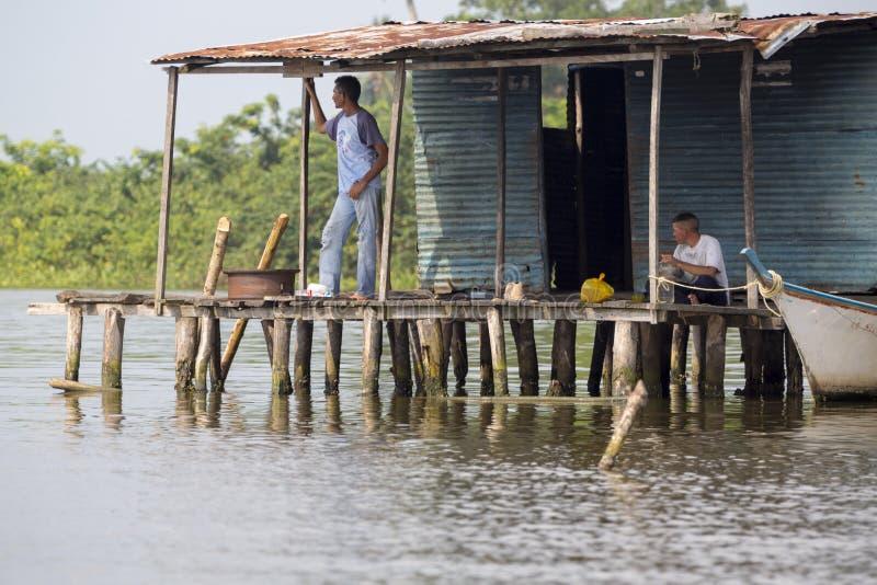 Uomini di Fisher che si siedono nelle povere case di legno alzate su Maracaibo fotografia stock
