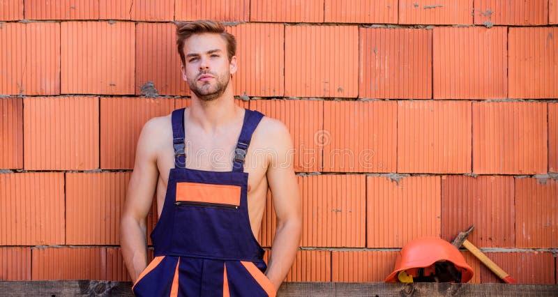 Uomini di lusso indossano le tute Pausa per rilassarsi Sexy laborer Lavoratore Attraente Costruzione Sfondo parete mattone lavora immagine stock