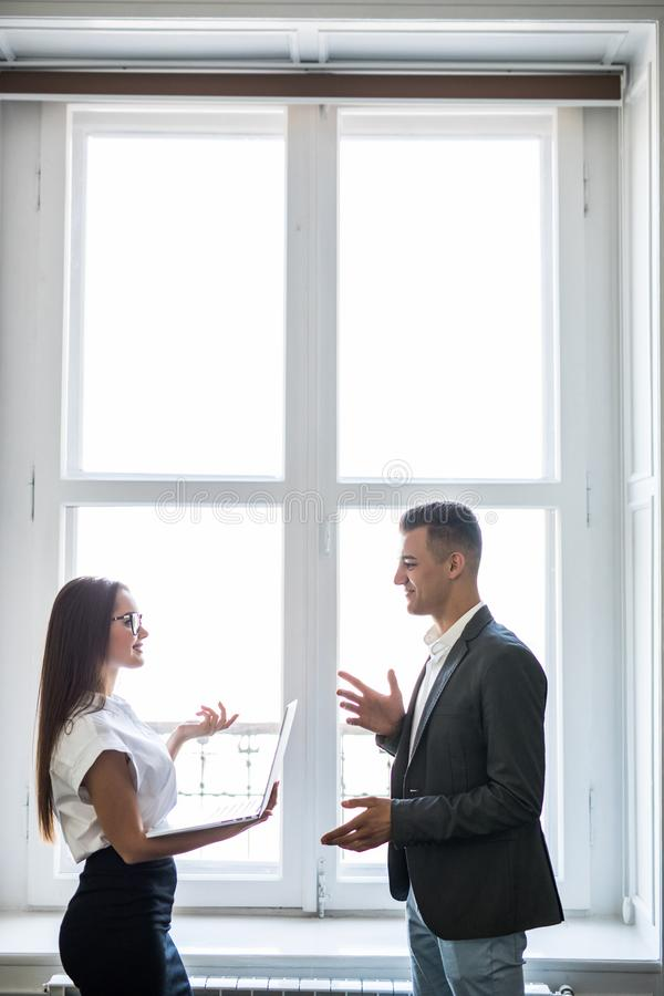 Uomini e donne di affari che parlano con un sorriso sui precedenti di grandi finestre in un centro di affari moderno fotografia stock