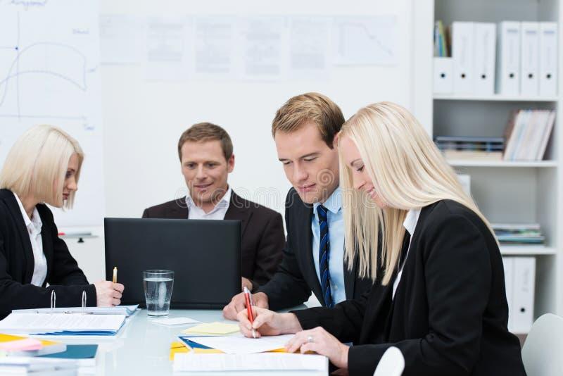 Uomini e donne di affari in una riunione immagine stock