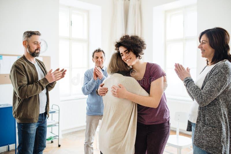 Uomini e donne durante la terapia del gruppo, mostrante un segno di sollievo immagine stock