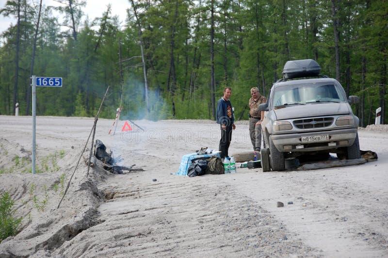 Uomini e riparazione dell'automobile alla strada Kolyma della ghiaia alla strada principale di Magadan a Y immagine stock