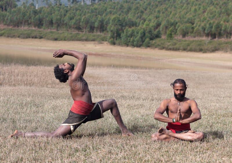 Uomini indiani che fanno esercizio di yoga su erba verde nel Kerala, India del sud fotografie stock libere da diritti