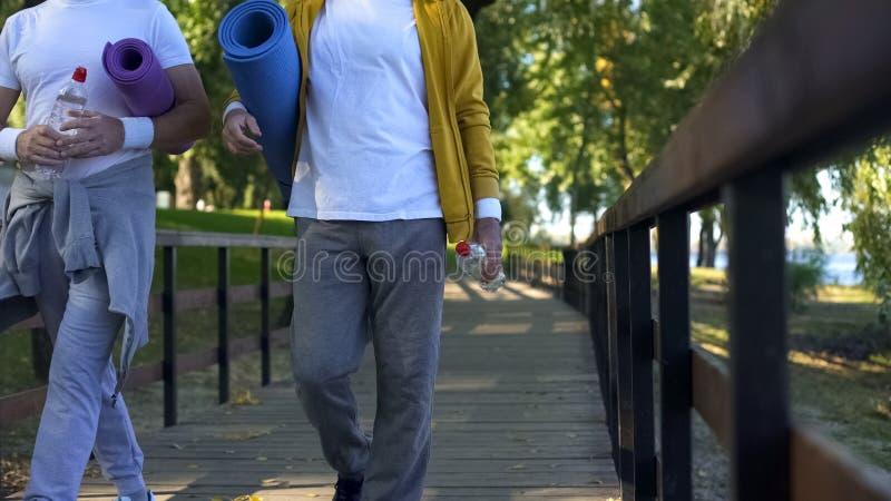 Uomini maturi allegri che camminano nel parco con le stuoie di yoga e le bottiglie di acqua, allenamento immagini stock libere da diritti
