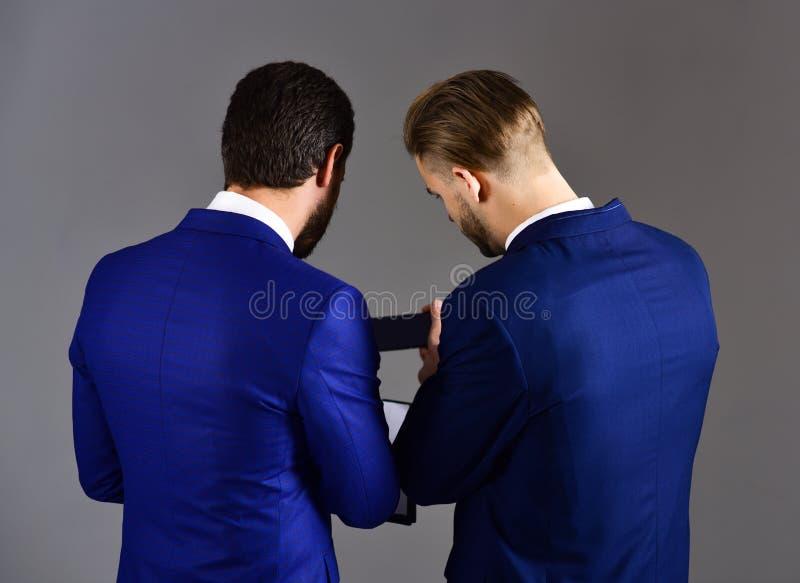 Uomini nel documento cartaceo della tenuta degli uomini d'affari o del vestito immagine stock