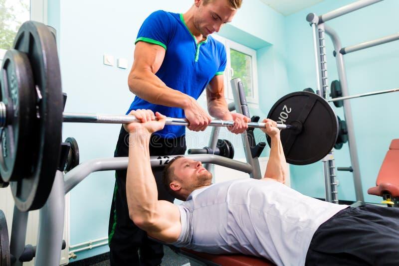 Uomini nell'addestramento della palestra di sport con il bilanciere per forma fisica fotografie stock libere da diritti