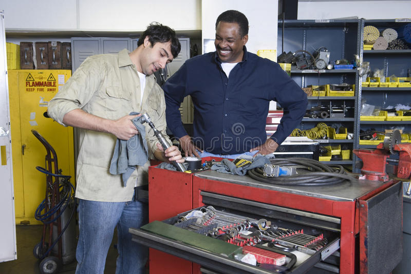 Uomini in officina con gli strumenti immagini stock libere da diritti