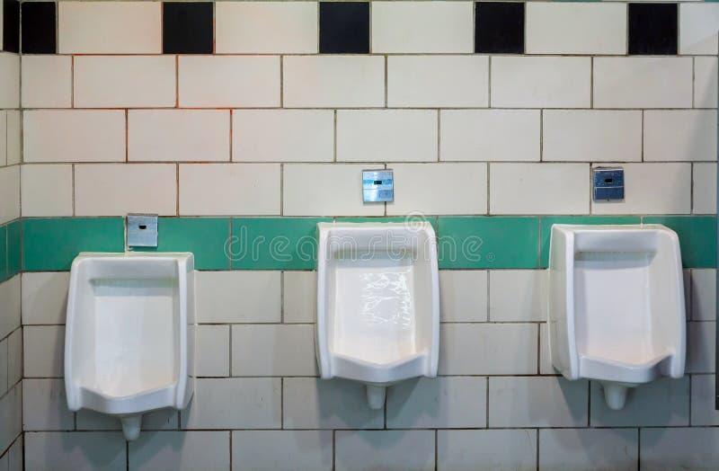 Uomini in orinali della stanza della toilette in una costruzione per gli uomini soltanto, orinali bianchi in men' bagno di s immagini stock