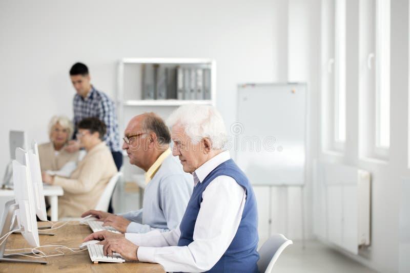 Uomini più anziani che per mezzo dei computer fotografie stock