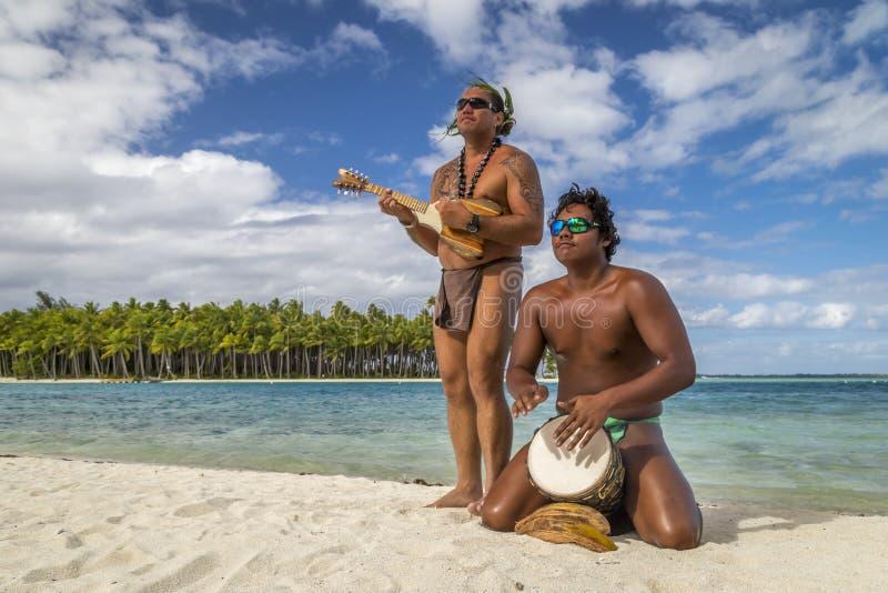 Uomini polinesiani che giocano gli strumenti tradizionali sulla spiaggia di Bora Bora - Polinesia francese fotografia stock libera da diritti