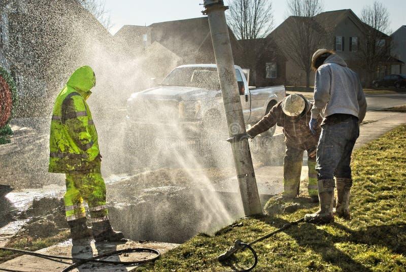 Uomini pratici fangosi del lavoratore che riparano la linea di galleggiamento rotta fotografie stock