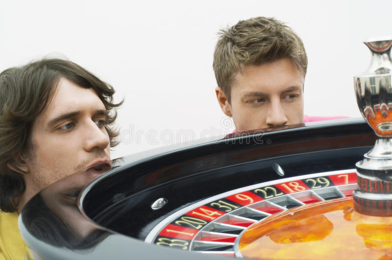 Uomini promettenti che guardano il pattinamento delle roulette fotografia stock