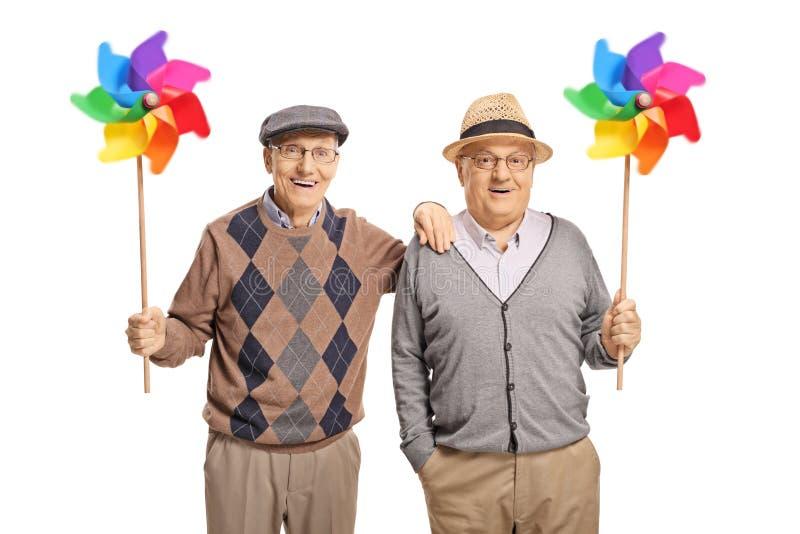 Uomini senior felici che tengono le girandole immagine stock libera da diritti