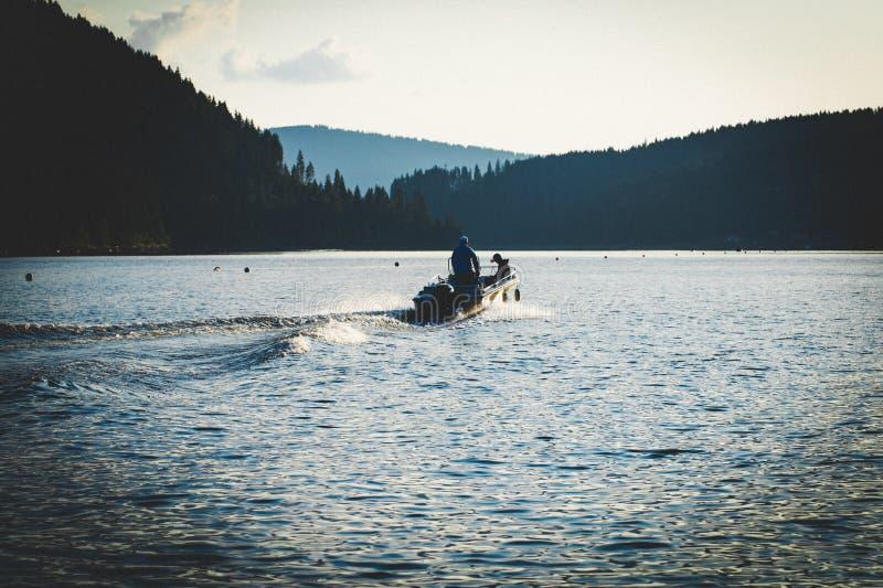 Uomini sulla barca sul lago Botte di uomini immagine stock
