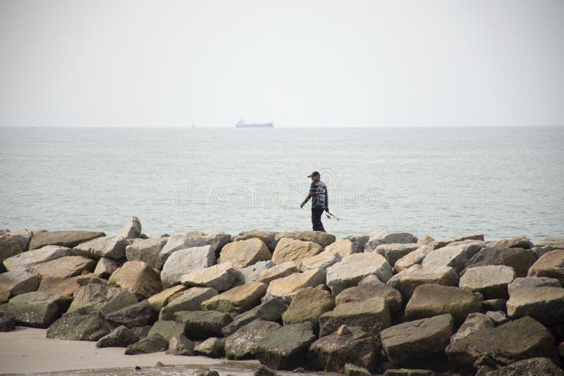 Uomini tailandesi che stanno e che pescano o che si inclinano nel mare alla spiaggia di Pae di divieto in Rayong, Tailandia fotografia stock libera da diritti