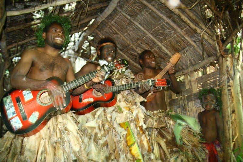 Uomini tribali del villaggio della Vanuatu che giocano chitarra immagine stock