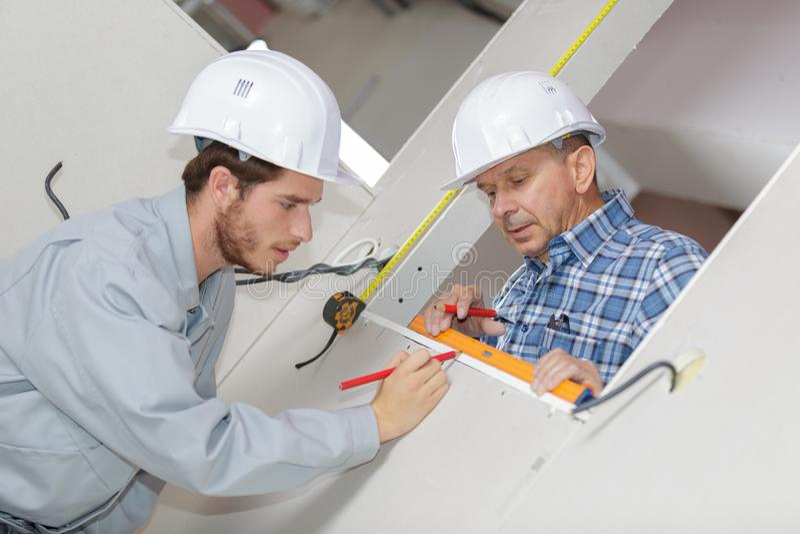 Uomini in uniforme ed elmetti protettivi che misurano parete con nastro adesivo fotografia stock