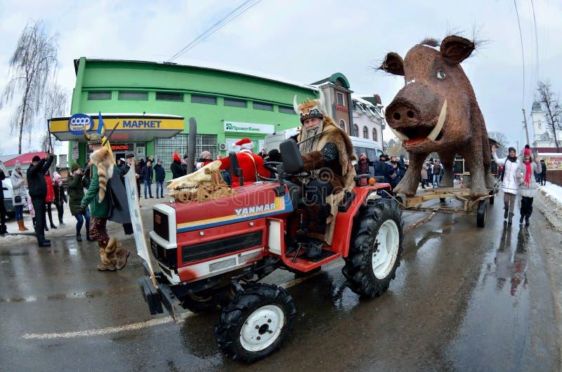 Uomini vestiti come guerrieri di vichingo con la statua enorme della cartapesta del simbolo selvaggio del maiale dell'anno al car immagine stock libera da diritti