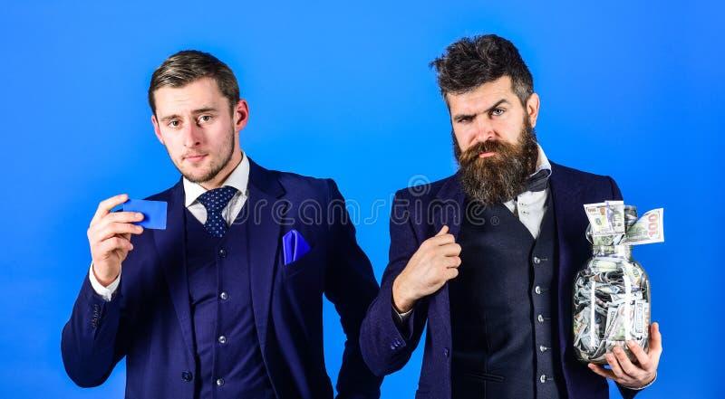 Uomini in vestito, uomini d'affari con il barattolo pieno di contanti e carta di credito, fondo blu Concetto del consulente in ma fotografia stock