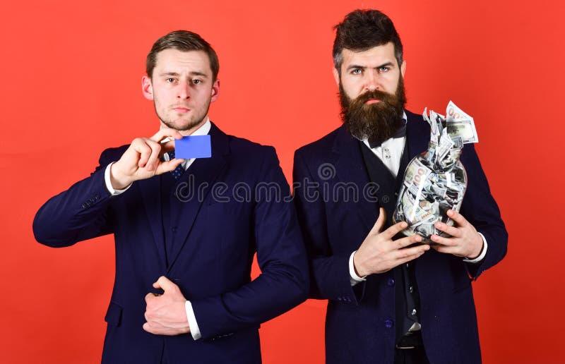 Uomini in vestito, uomini d'affari con il barattolo pieno di contanti e carta di credito, fondo rosso L'uomo maturo ed il tipo mo fotografie stock libere da diritti