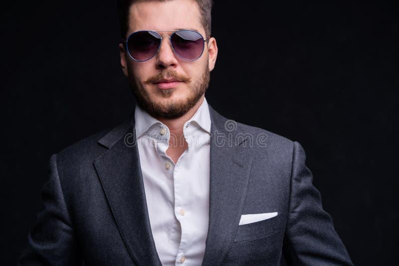 Uomini in vestito pieno Integrale di giovani uomini d'affari sicuri in occhiali da sole che stanno isolati sul nero fotografia stock