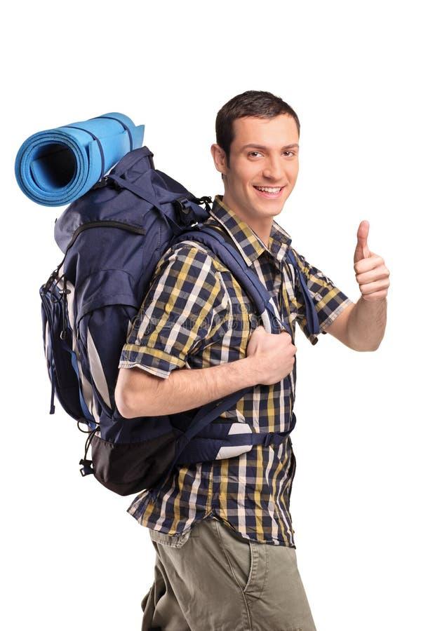 Uomo in abiti sportivi con lo zaino che dà pollice in su fotografia stock libera da diritti