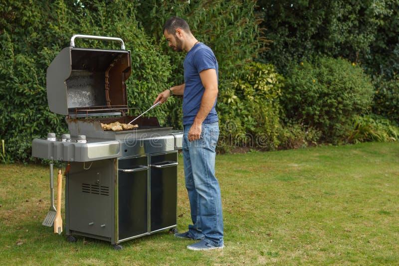 Uomo ad una griglia del barbecue immagini stock