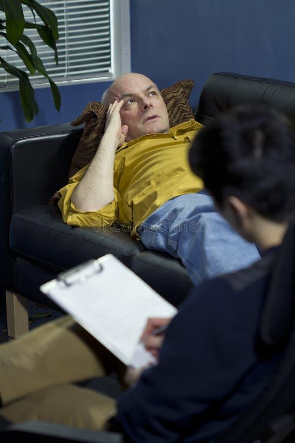 Uomo ad una sessione di terapia che parla dei suoi problemi fotografie stock libere da diritti