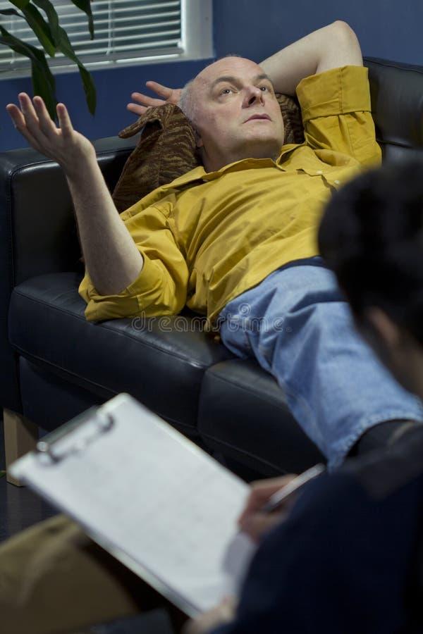 Uomo ad una sessione di terapia che parla dei suoi problemi immagini stock libere da diritti