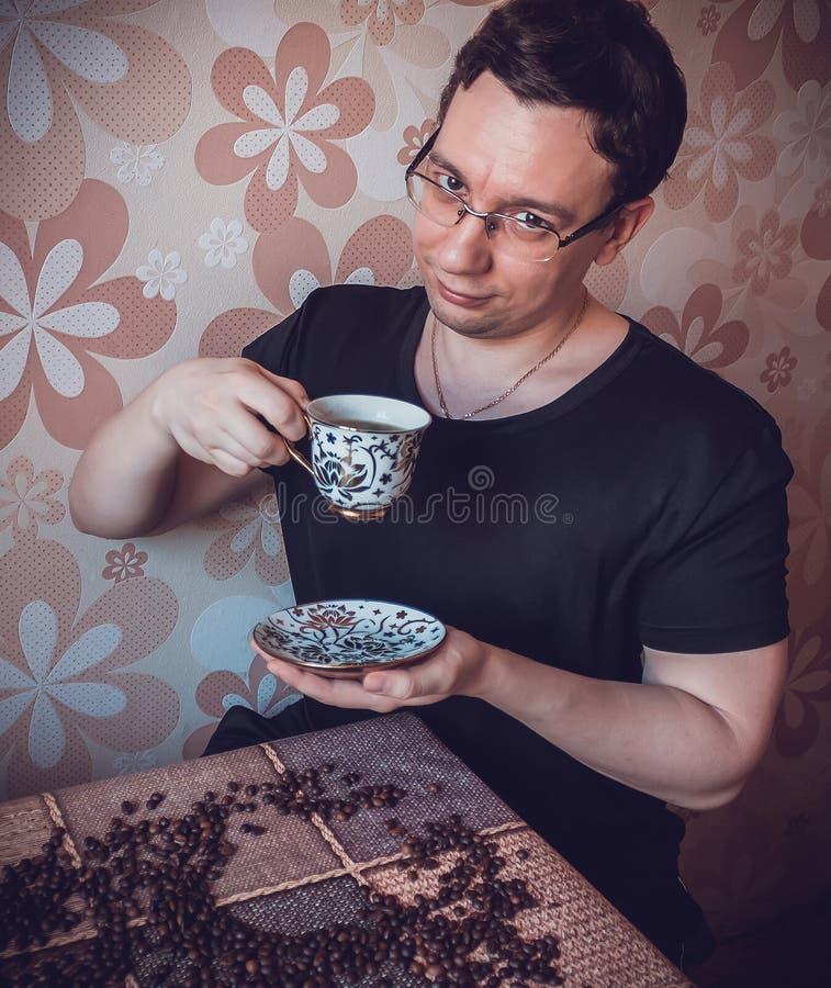 Uomo ad una tazza di forte caffè fresco ad un assaggio fotografie stock