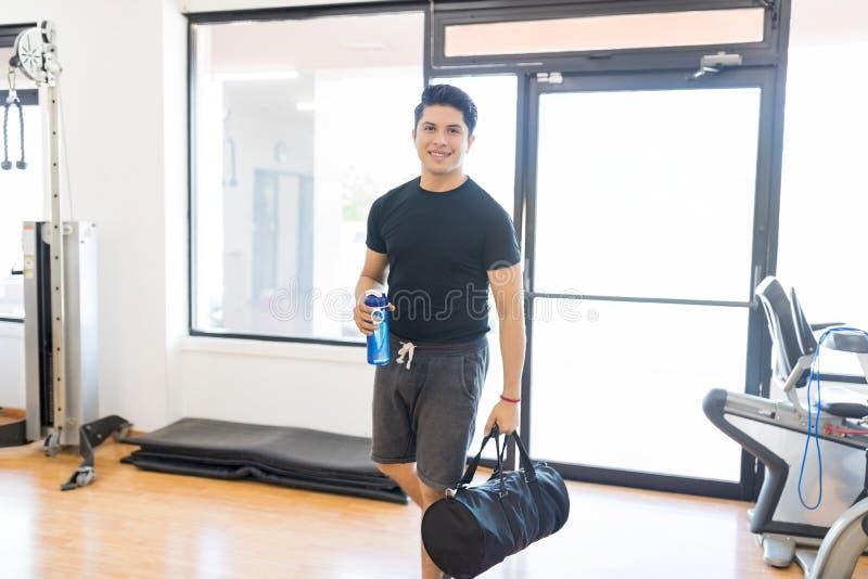 Uomo adatto con la bottiglia di acqua e borsa che entra nella palestra immagini stock