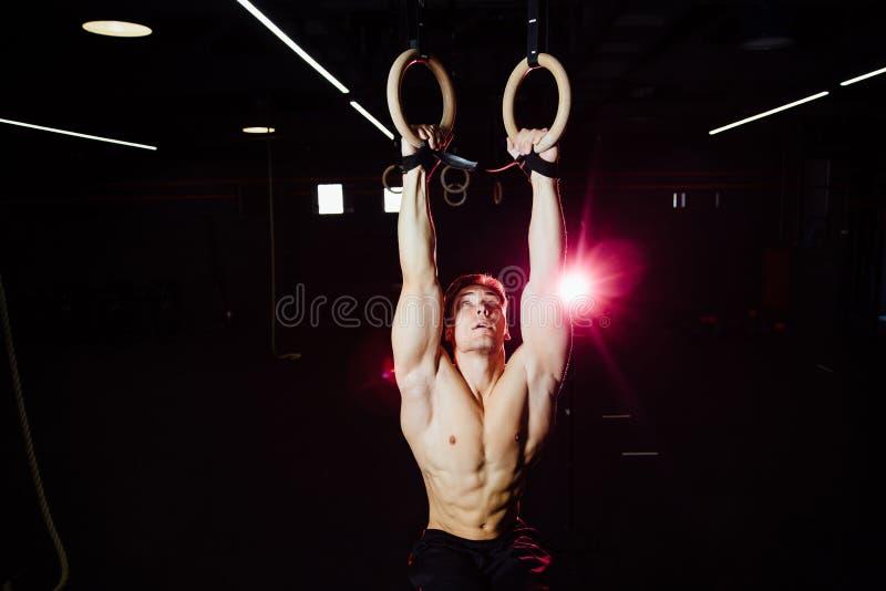 Uomo adatto dei giovani che tira su sugli anelli relativi alla ginnastica fotografie stock libere da diritti