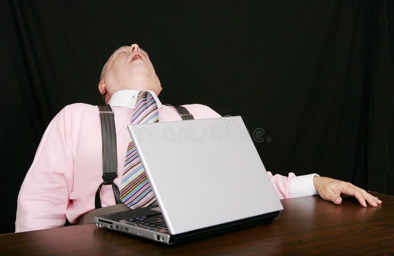 Uomo addormentato di affari al suo scrittorio immagine stock libera da diritti