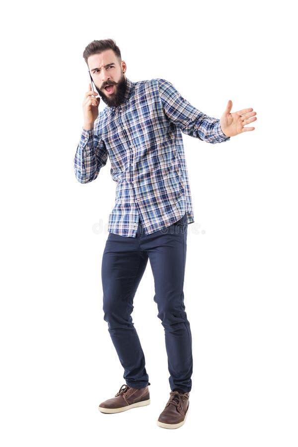 Uomo adulto barbuto arrabbiato che urla sul telefono cellulare che gesticola con la mano immagine stock libera da diritti