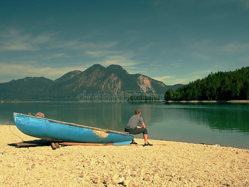 Uomo adulto in camicia blu al vecchio crogiolo di pagaia di pesca nel lago delle montagne immagine stock libera da diritti