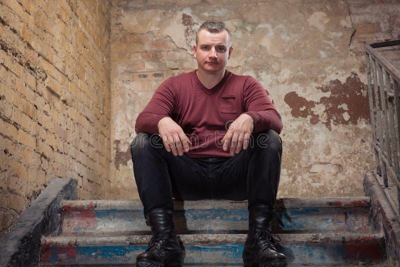 Uomo adulto caucasico brutale in maglione o pullover rosso che si siede sulle scale di pietra con il fronte serio contro il fondo fotografie stock