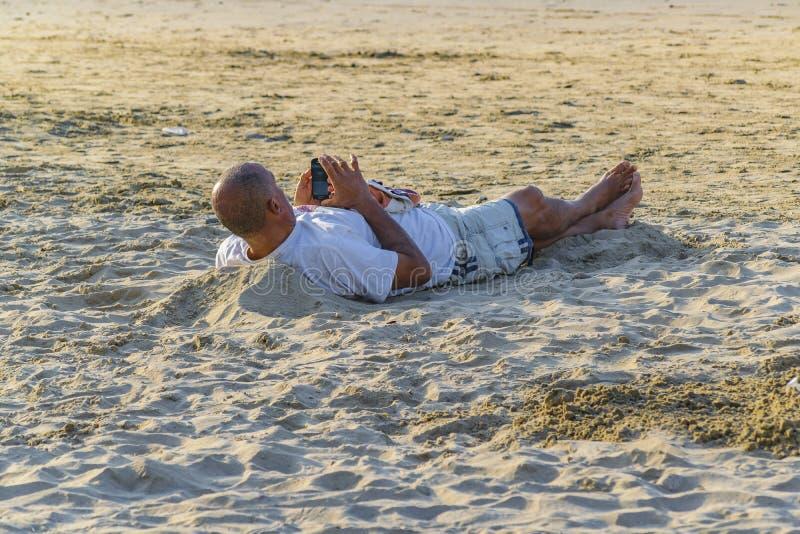 Uomo adulto che riposa alla sabbia fotografie stock